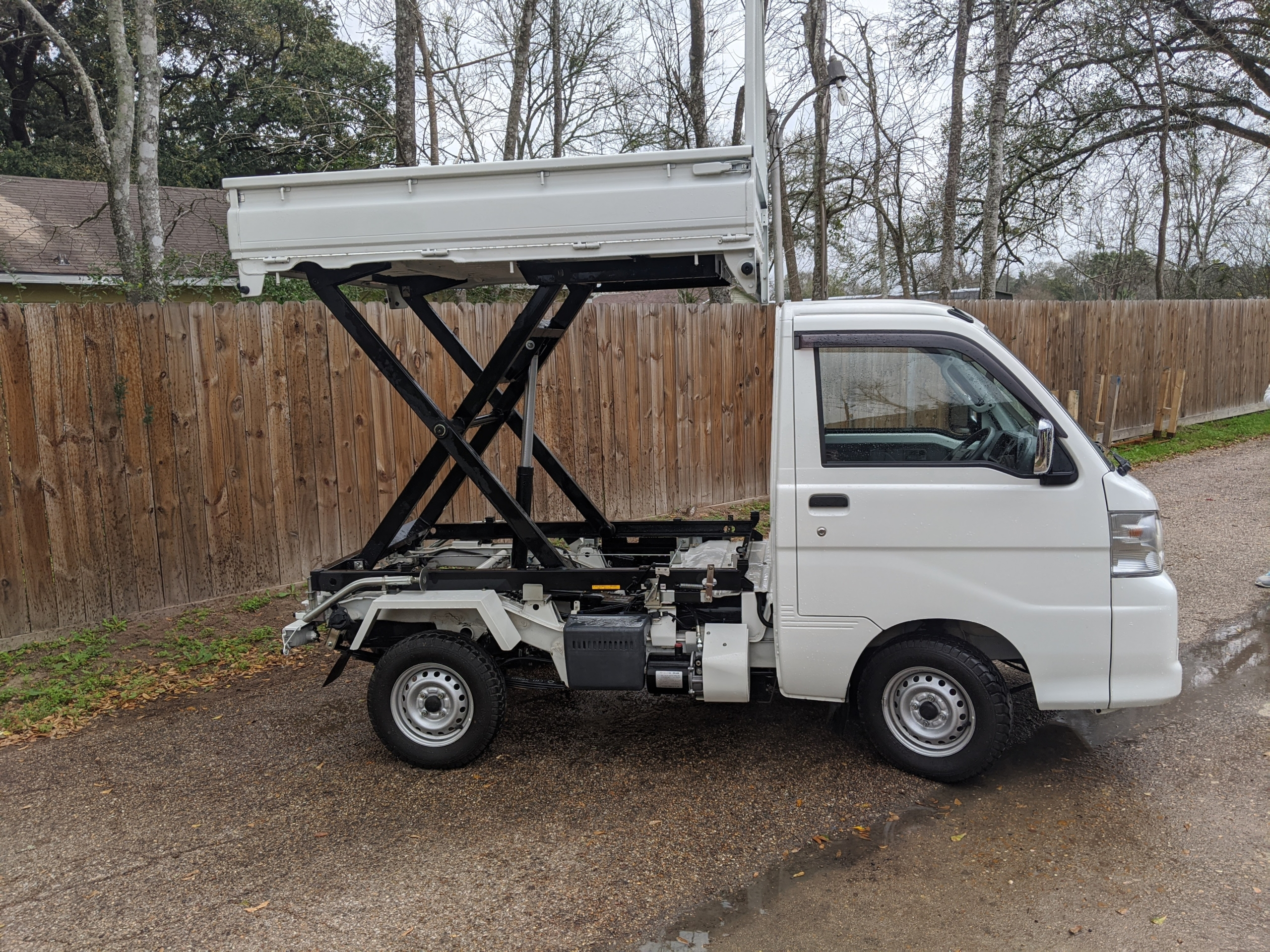 A picture of a scissor lift Kei truck bed in the air.